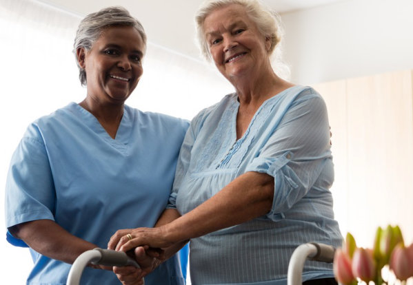 elder woman with caregiver standing side by side