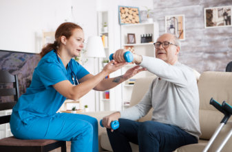 senior man in nursing home with doing physical therapy with help from nurse using dumbbells