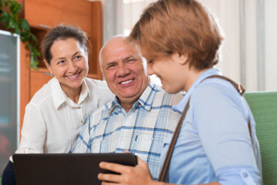 senior couple answer questions of social worker with laptop in home