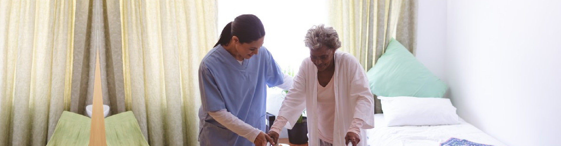 caregiver assisting elder woman in using a walker