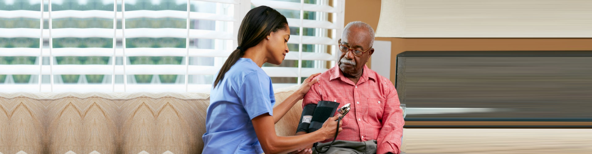 caregiver getting elder man's blood pressure