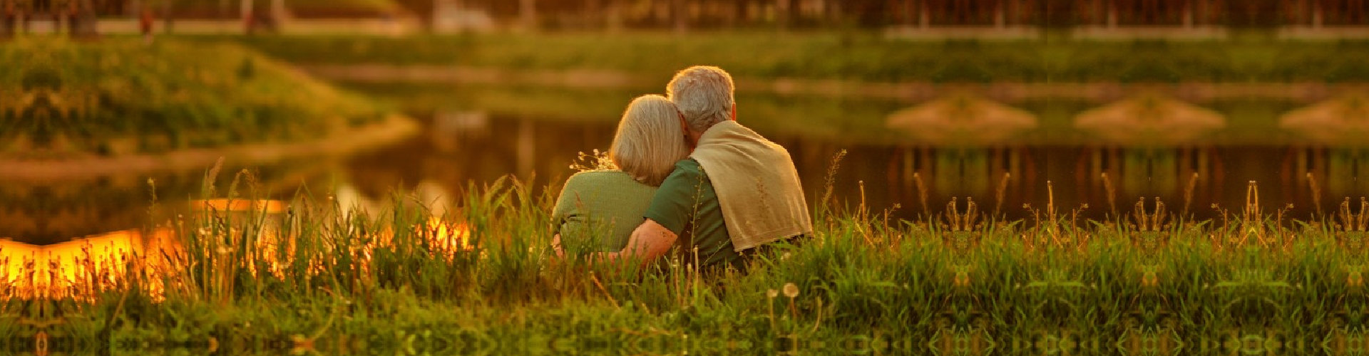 elderly couple sitting by the fields hugging